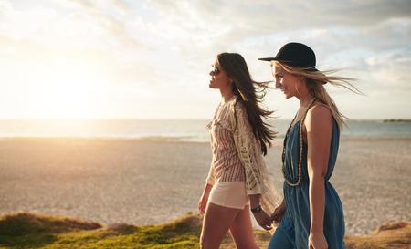 Vackra unga kvinnor promenader på en strand. Två vänner går på stranden på en sommardag och njuter av semester.