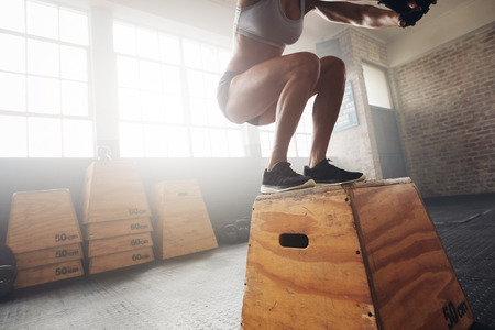 Fit young woman box jumping at a crossfit gym. Female athlete is performing box jumps at gym, with focus on legs.