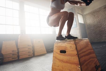 Fit jonge vrouw doos springen op een crossfit sportschool. Vrouwelijke atleet voert boxsprongen uit bij sportschool, met focus op benen.