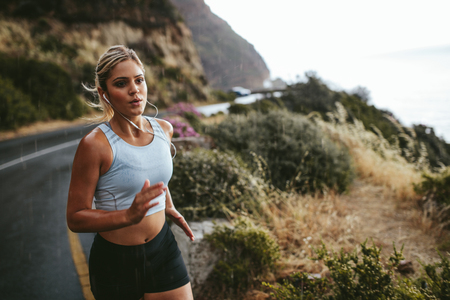 Shot of young fitness woman running outdoors in countryside. Determined female athlete training on road. Stockfoto