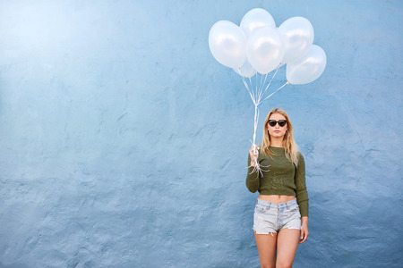 white people: Horizontal shot of attractive female fashion model holding balloons against blue wall. Attractive young woman holding white balloons with lots of copy space. Stock Photo
