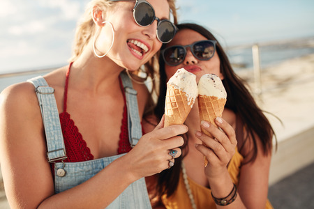 Portrait of two young women standing together eating ice cream. Happy young female friends outdoor.