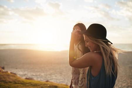 niñas bonitas: Dos jóvenes amigas que caminan por la orilla del mar. hermosas mujeres jóvenes que dan un paseo a lo largo de una playa. Foto de archivo