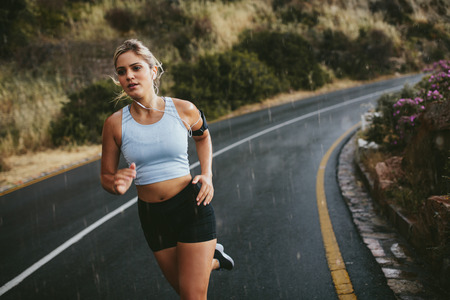 Fit young woman jogging outdoors on highway. Female athlete training running on a rainy day. 版權商用圖片