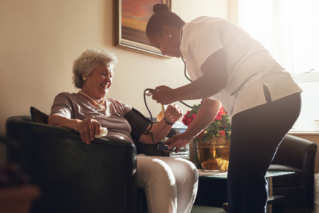 Nurse measuring blood pressure of senior woman patient in retirement home. Home caregiver doing routine checkup of a mature female patient. photo