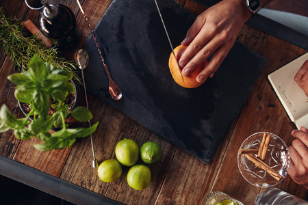 two on top: Bartender cutting a grapefruit on the chopping board with another taking down notes. Men experimenting with creating cocktail drink.