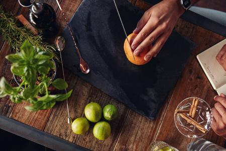 cuchillo: Camarero cortar un pomelo en la tabla de cortar con otro tomando notas. Los hombres que experimentan con la creación de cóctel.