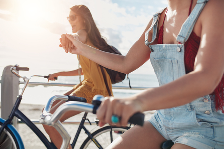 Two female friends holding hands and riding cycles on the seaside promenade. Happy young women enjoying riding bicycles on a summer day.