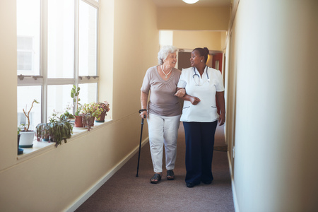 Full length portrait of senior woman walking with her nurse at nursing home. Healthcare work helping female patient.