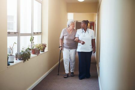 persona caminando: Retrato de cuerpo entero de la mujer mayor que recorre con su enfermera en el hogar de ancianos. trabajo en salud ayudando paciente. Foto de archivo