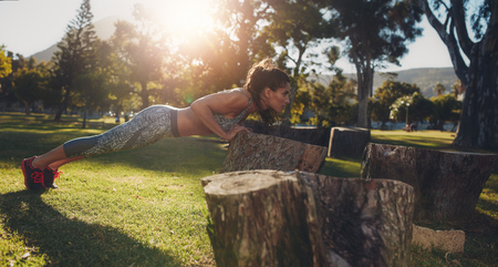 Tough young woman doing pushups on a log at park. Horizontal shot of a fit young female athlete exercising in nature.
