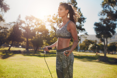 woman rope: Outdoor shot of determined woman skipping outdoors in nature. Fitness female exercising with jump rope in a park on a sunny day.