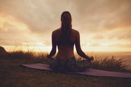 woman sunset: Silhouette rear view of young woman doing yoga meditation outdoors. Fitness female model sitting on exercise mat in lotus yoga pose during sunset. Stock Photo