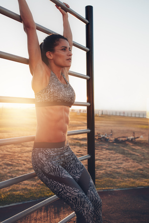 effort: Image of fit young woman training outdoors at sunset. Fitness woman doing stretching on wall bars.