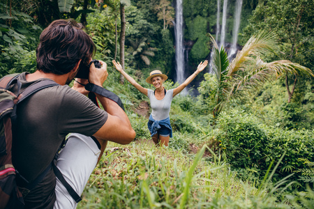 waterfall model: Male photographer taking pictures of a young woman standing in front of waterfall in forest. Couple enjoying a day in forest. Stock Photo