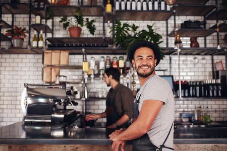 음료를 만드는 카운터 뒤에 일하고 바리 스타와 서 커피 숍 소유자.