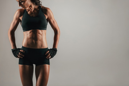 emphasise: Athletic woman with strong abdominal muscles posing with her hands on her hips in shadowed light to emphasise her physique, with copy space