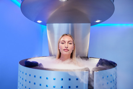 the whole body: Woman in cryosauna booth for whole body cryotherapy. Caucasian female in freezing chamber with nitrogen vapors.