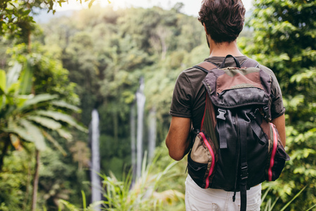 admiring: Rear view shot of male hiker with backpack standing on a cliff and looking at waterfall. Young man admiring the landscape in forest.