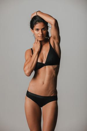 jungen unterwäsche: Lächelnde herrliche junge Frau in sexy Unterwäsche schwarze Unterwäsche posiert mit ihren Armen hob ihren schlanken durchtrainierten Körper vorführt