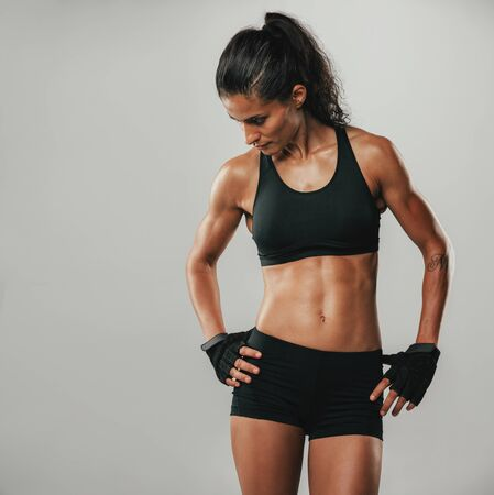 Muscular athletic young woman in sportswear posing with her hands on her hips looking down, square format on grey Stock Photo