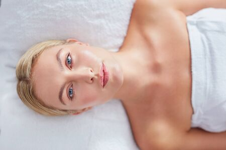 dayspa: Top view of pretty young woman lying on massage table at dayspa. Woman with beautiful face and blue eyes.