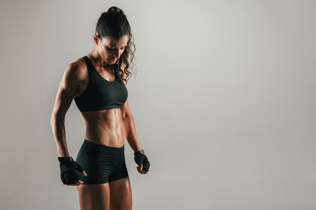 Strong muscular woman in tight black shorts and weight lifting gloves over gray background with copy space