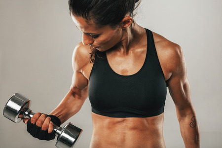 cropped out: Strong healthy young women lifting weights working out with dumbbells, close up of her flexing her arm to strengthen her muscles Stock Photo