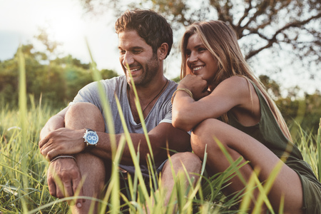 Portrait of smiling young couple in love sitting together outdoors in field. Happy young man and woman in meadow.