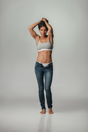 Sexy shapely young woman in her lingerie and unzipped blue jeans standing with her hands raised to her long dark hair over a grey background