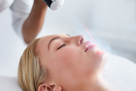 resurfacing: Close up of face of young woman receiving local cryotherapy. Beauty treatment using vaporized nitrogen.