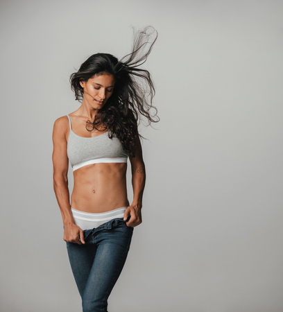 demure: Sexy young woman posing in her underwear and unzipped jeans looking down seductively with her long dark hair blowing in the breeze, isolated on white in square format