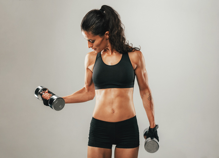 Fit woman in pony tail lifting chrome dumbbell weights over gray background with copy space on either side