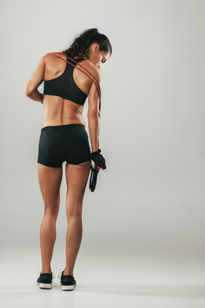 Back view of pretty muscular woman in grey room with exercise bands across her shoulders