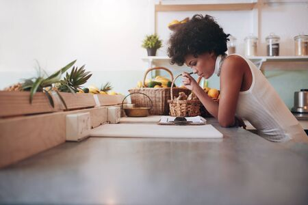 proprietor: Female proprietor of a juice bar calculating a her business expenses. African young woman looking at the clip board on counter.