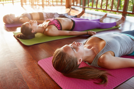 Shot of yoga class with young women relaxing on floor. Yoga class lying in the Corpse pose, Savasana.