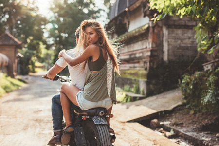 couple outdoor: Rear view shot of attractive young woman sitting on back of her boyfriend riding bike through village road.