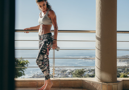 mascular: Shot of muscular young female standing in the balcony with water bottle. Fit woman taking break from workout. Stock Photo