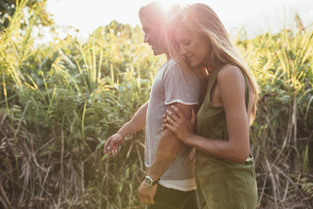countryside loving: Side portrait of loving young couple walking in countryside. Beautiful young woman walking with her boyfriend outdoors on a sunny day.