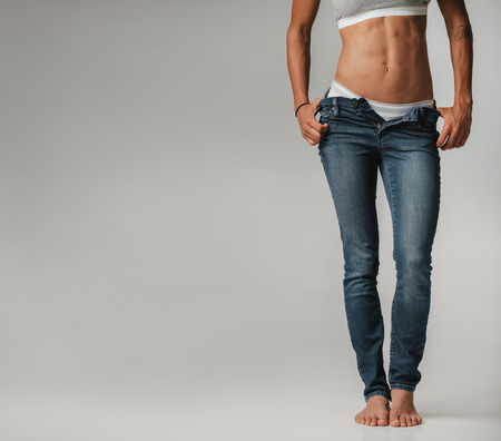 lower body: Sexy toned young woman posing with unzipped jeans in her panties and bra in a relaxed pose with thumbs in her pockets, body view isolated on grey with copy space Stock Photo