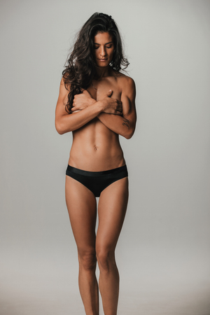 Tall single beautiful woman in black panties covering chest over gray background with copy space