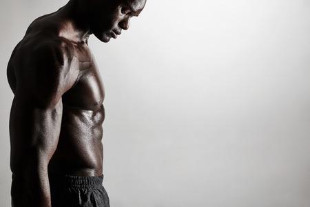 Close-up do homem Africano sem camisa, de pé contra um fundo cinza. Imagem colhida do torso de um homem musculoso com copyspace.