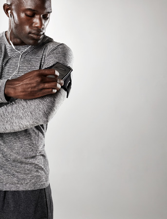 black male: Shot of young black male model listening to music on cell phone. Man with mobile phone armband standing against grey background with copy space.