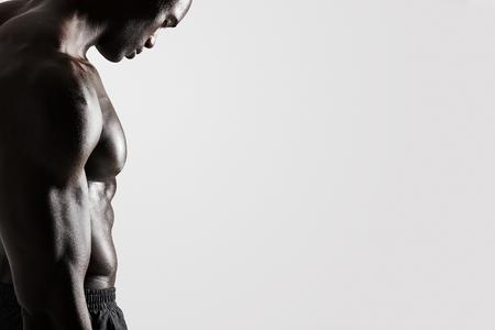 modelos hombres: Vista lateral recortar foto de hombre joven con cuerpo musculoso de pie sobre fondo gris con un montón de espacio de la copia. Foto de archivo