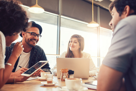 Portrét šťastné mladých přátel sedí a mluví v kavárně s digitálním tabletem a notebookem