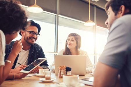 Portret szczęśliwych młodych przyjaciół siedzi i rozmawia w kawiarni z cyfrowym tablecie i laptopie