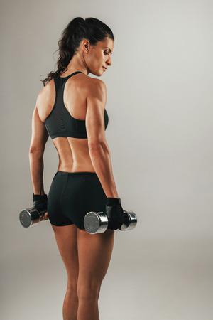 Drie kwart zicht op de rug van de romp en dijen mooie vrouwelijke atleet met pony staart en zwarte outfit terwijl halters over grijze achtergrond