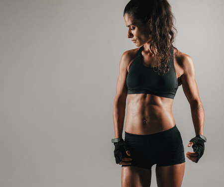 weightlifting gloves: Muscular single woman with long hair and firm abdominal muscles looking over gray background with copy space Stock Photo