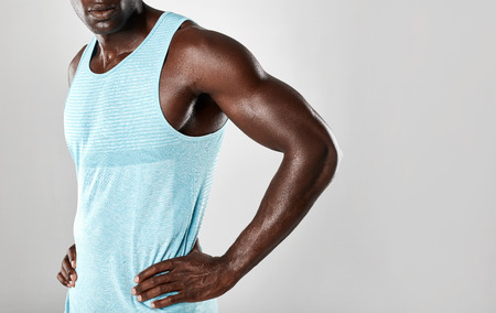 cropped shot: Cropped shot of muscular young african man standing with hands on hips against grey background with copy space. Stock Photo