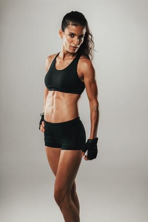 cuerpo femenino: Mujer bonita en pantalones cortos deportivos mira fijamente a la cámara mientras posando sobre un fondo gris